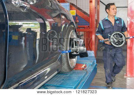 Bangkok, Thailand - January 16, 2016 : Unidentified serviceman checking suspension in a car at garage
