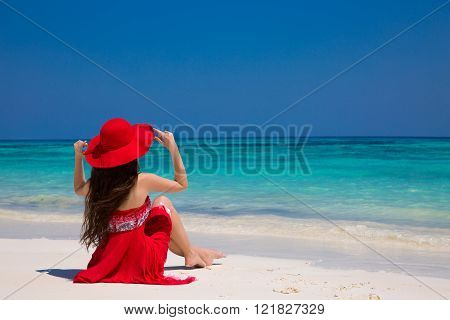 Beauty fashion woman in red hat enjoying beach relaxing joyful on white sand in summer by tropical blue water. Bliss freedom beach concept. Good life. Vacation.