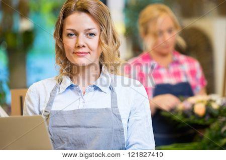 Portrait Of Beautiful Female Florist In Flower Shop