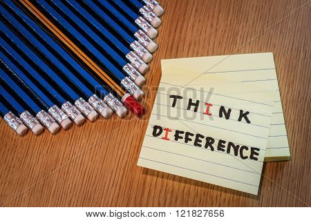 Red pencil standing out from crowd of blue pencils and post it of differrent thinking word on wooden table. Business success concept