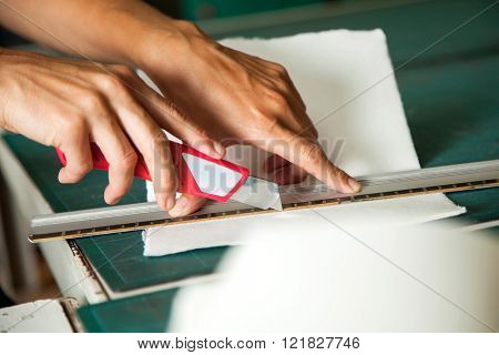 Hands Cutting Paper Using Blade On Table