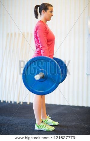 Fit Woman Lifting Barbell At Gym