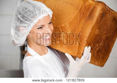 Closeup Of Baker Smiling While Carrying Big Bread Loaf