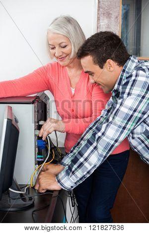 Tutor Assisting Senior Student Setting Up Computer