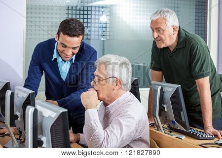 Happy Instructor Explaining Senior Men In Computer Class