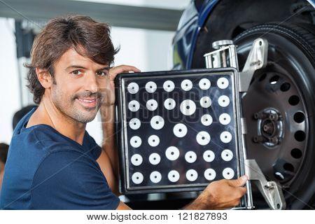 Confident Mechanic Adjusting Wheel Aligner On Car