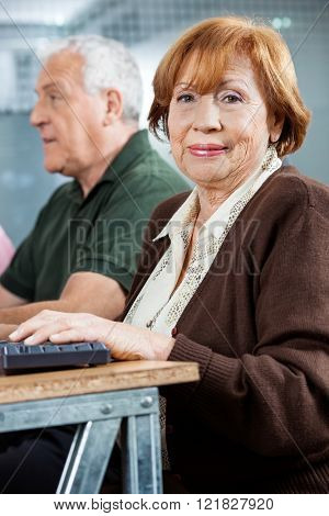 Confident Senior Student Sitting In Computer Class