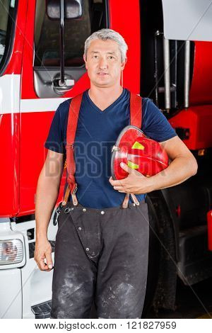Confident Firefighter Holding Red Helmet