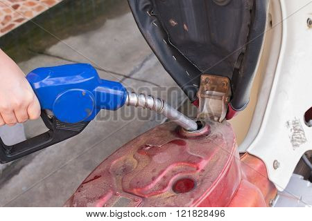 Add benzine fuel to motorcycle at a gasoline station with a hand