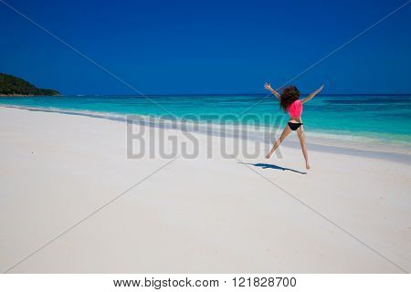Beautiful Women. Happiness bliss freedom beach concept. Enjoyment. Girl Model jumping on exotic beach with white sand and blue water. Travel. Free. Vacation.