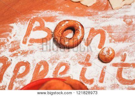 The inscription bon appetit on the table with flour