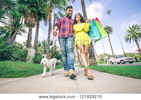 Couple walking outdoors with poodle dog and holding shopping bags