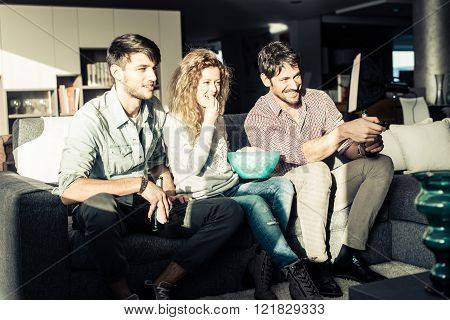 Group of friends watching a movie at home in the evening - Cheerful people having fun while relaxing in the living room