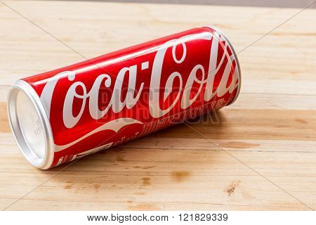 PHARE THAILAND - MARCH 3 2016. Coca Cola can on wooden table. Coca Cola drinks are produced and manufactured by The Coca-Cola Company an American multinational beverage corporation.