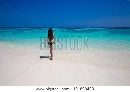 Enjoyment. Beautiful bikini woman walking on tropical beach, slim girl with long hair entering the sea water with white sand on a hot summer day. Wellness. Bliss freedom concept. Back shot