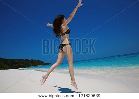 Summer vacation. Happy woman running and jumping on exotic beach, brunette girl model playing on the ocean coast. Vacation. Travel. Bliss freedom concept.