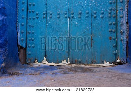 rotted bottom of a blue wood door decorated with metal studs, Chefchaouen, Morocco