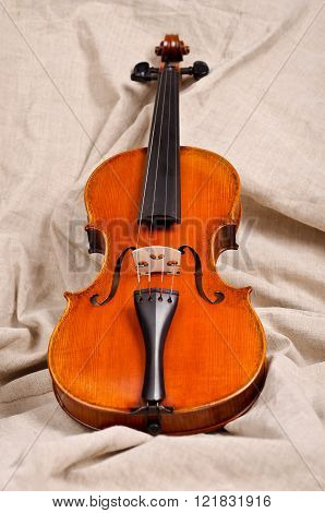 Wooden violin on beige background. Harmony melody