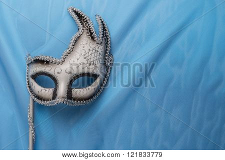 Colorful carnival mask on wavy blue satin fabric background.