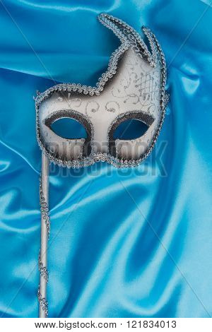 Colorful carnival mask on wavy blue satin fabric background. Top view with copy space.