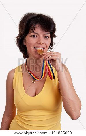 Happy young woman with gold medal between her teeth trying metal hardness