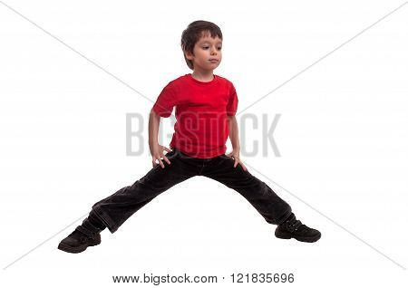 Little boy in red t-shirt trying to do splits isolated on white background