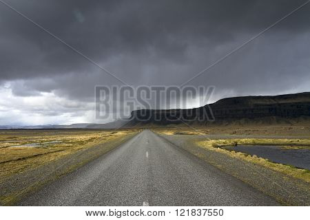 Horizontal photo of a straight asphalt road going into the mountains with storm clouds ahead in the south of Iceland