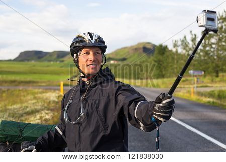 Happy biker doing selfie on backdrop of mountains in Iceland