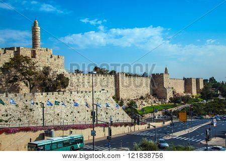 David's Tower dominates the walled Old City of Jerusalem. Passenger bus moves through the city streets