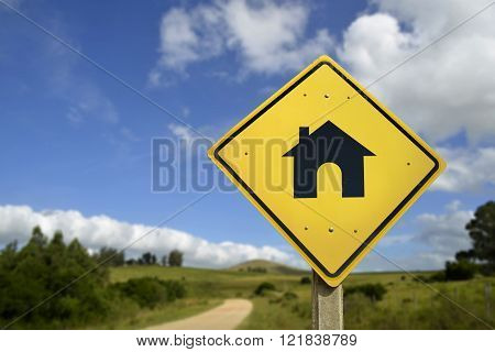 Buy your own house in the countryside way to the home of your dreams concept. Road sign with real estate icon in nature rural environment includes copy space.