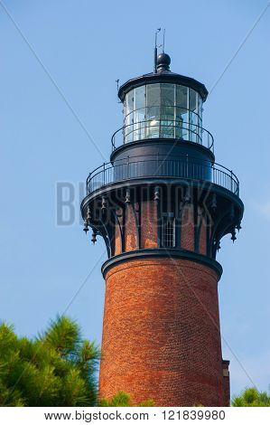 Beautiful colorful Lighthouse along ocean coast close up fresnel lens lighting navigation for ships at sea
