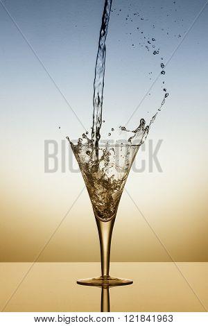 Water Fall Into A Glass And Splash On Blue And Orange Background