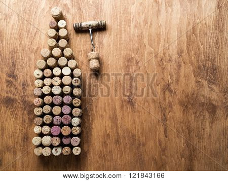 Wine corks in the shape of wine bottle on the wooden background.