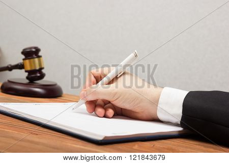 Lawyew working. Notary public signing document at his workplace.
