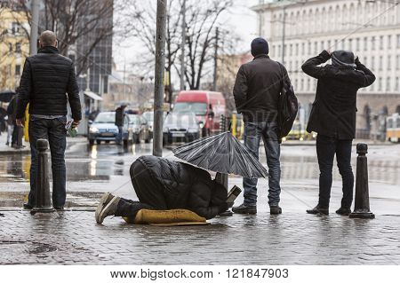 Homeless Beggar With Umbrella In The Rain