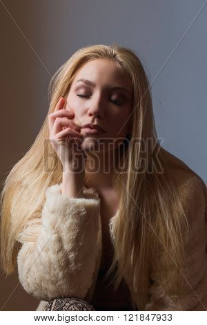 Close up portrait of young beautiful blonde sexy girl in wool coat on wall background, retro look