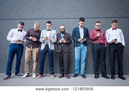 Group of elegant young businessmen standing against the wall and checking their mobile phones.