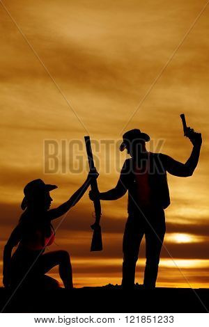 A silhouette of a cowgirl handing her cowboy his weapons.