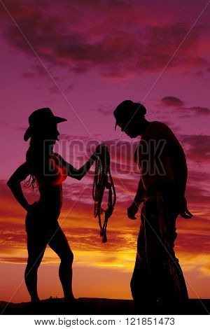 A silhouette of a cowgirl handing over her rope to her cowboy.