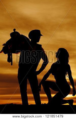 a silhouette of a woman kneeling down in front of her cowboy while he is holding onto a saddle.