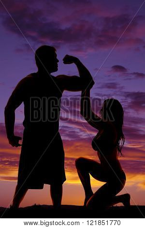 A silhouette of a woman, kneeling down, while reaching up to touch her man's arm muscles.