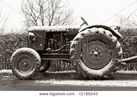 black and white photograph of classic old tractor in winter