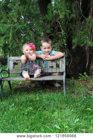 Sister and brother pose side by side. Brother leans over back of park bench and sister sits on seat.