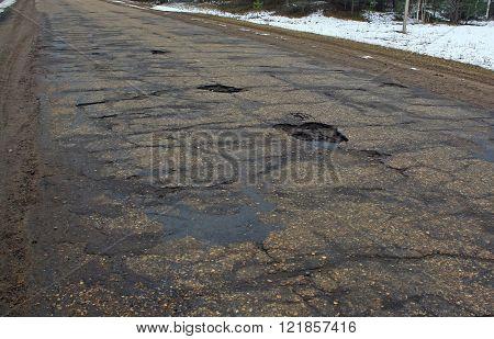 shot of potholes in asphalt on rural road