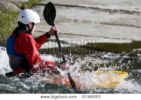 a whitewater kayaker surfing on a wave