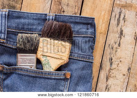 Two paint brushes in jeans pocket on wooden table