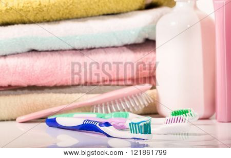 Towel hairbrush and toothbrushes in pastel tones. Focus on a near toothbrush the small depth of sharpness