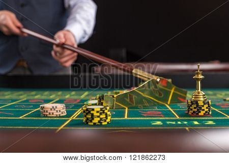 Croupier collects chips using stick in casino.
