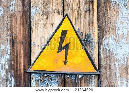 Old yellow high voltage caution sign hanging on the grunge wooden boards