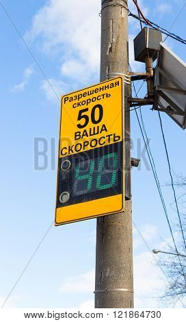 Police speed camera radar warning on street in city. Text in russian: